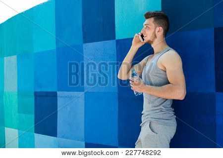 Young Sporty Man Talking On Phone, Having Break In Workout, Standing At Bright Blue Graffiti Wall, C