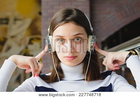 A Pretty Brunette Girl Is Listening To A Music In A Cafe In Her White Headphones