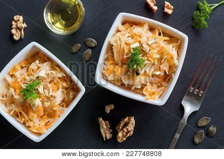 Fermented Cabbage And Carrots In Two Square Bowls On Dark Background, Top View