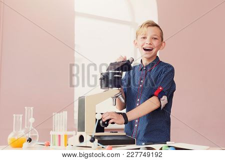 Happy Smiling Schoolboy Looking In Microscope During Lesson Of Chemistry Or Biology In School. Stem
