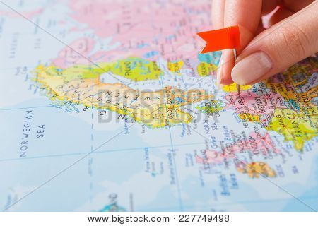 Travelling Background. Female Hand Tackling Country With Flag-pin On The Map. Tourism And Vacation C