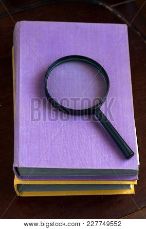 Two Closed Book And A Magnifying Glass