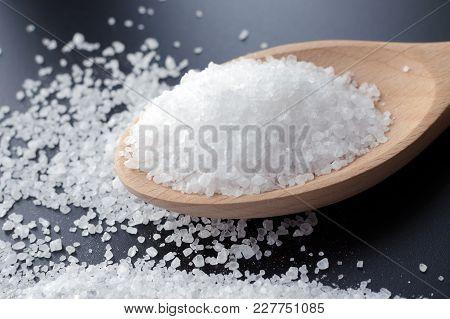 Sea Salt Crystals In Wooden Spoon Scattered Over Dark Grey Background, Healthy Food Concept