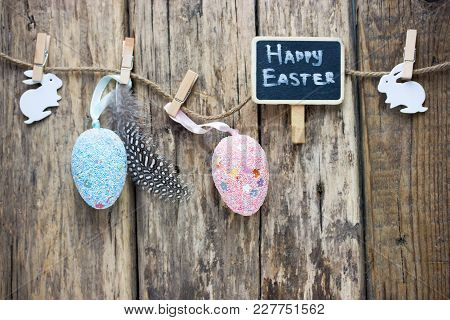 Easter Holiday Background With Eggs Bunnys Feathers Clothespins Decorations Hanging On Rope