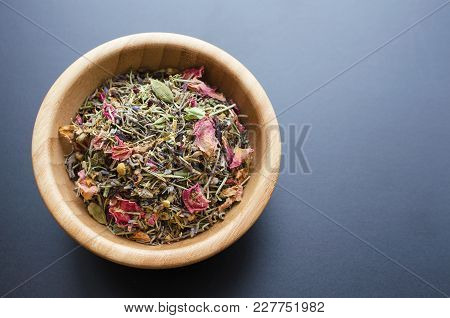 Dry Mountain Herbal Tea In Wooden Bowl Over Grey-blue Color Background, Copy Space