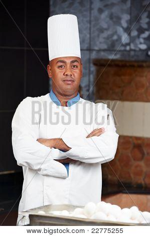 cheerful arab chef man in uniform standing at kitchen