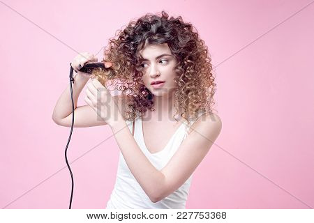 Beautiful Young Woman Making Curls With Curling Iron. Amazing Curly Shine Hair. Top View. Hair Styli