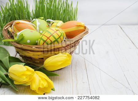 Easter Decoration With Eggs And Tulips On A Wooden Background