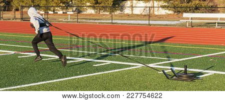A High School Track And Field Athlete Is Pulling A Sled With Weights On It Across A Green Turf Field
