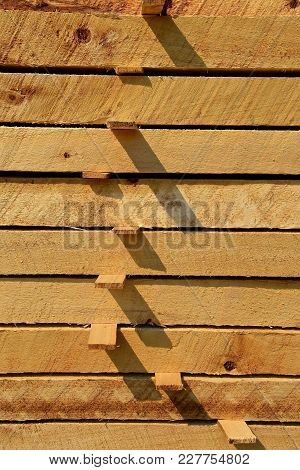 Stacked Rough Sawed Dimensional Lumber Is Pile With Laths Allowing For Circulation And Drying.