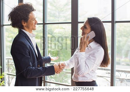 Cheerful Business Partners Concluding Deal And Shaking Hands In Modern Office. Positive Multiethnic