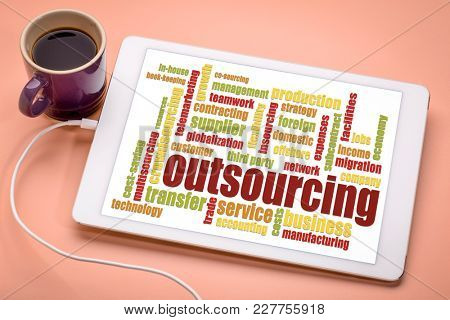outsourcing word cloud on a digital tablet with a cup of coffee