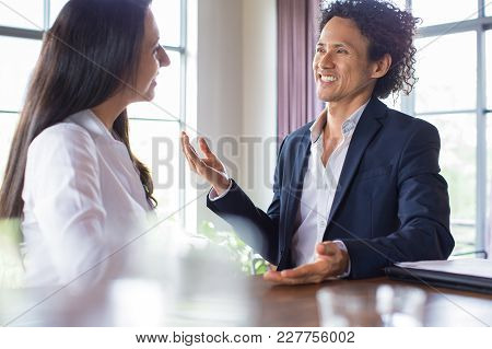 Excited Asian Man Talking To Business Partner In Cafe. Cheerful Enterprising Handsome Businessman Di