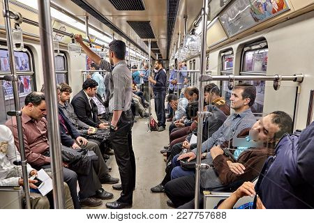 Tehran, Iran - April 29, 2017: Muslims Ride In The Subway Train, Iranian Men Stand And Hold On To Th