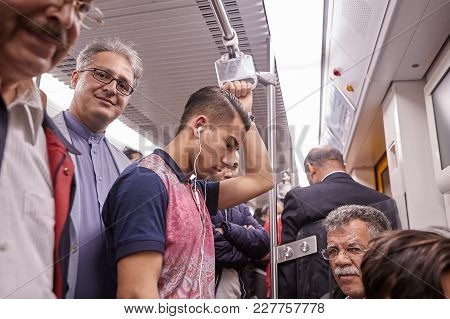 Tehran, Iran - April 29, 2017: Iranian Men Of Different Ages Ride The Subway, One Of Them Listens To