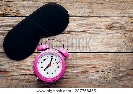 Black Sleeping Mask With Alarm Clock On Grey Wooden Table