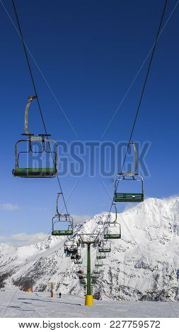 Chairlift At Italian Ski Area On Snow Covered Alps During The Winter - Winter Sports Concept