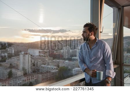 young man enjoying evening coffee and beautiful sunset landscape of the city while standing by the window