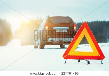 Emergency Stop Sign And Car On Winter Road At Sunset.