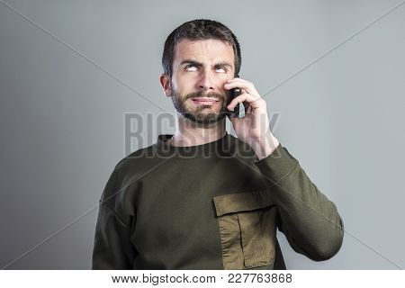 Bored And Frustrated Man Having A Dull Conversation Over His Cell Phone