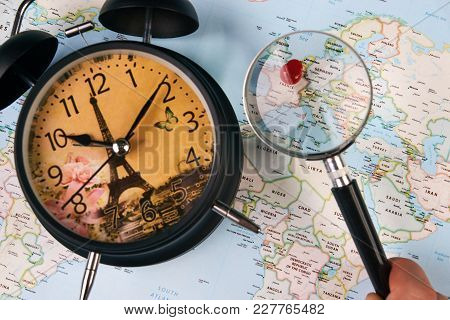 Planing For Travel To France Paris With Worldmap Globe Magnifying Glass And Alarm Clock. Travel Time