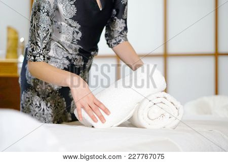 The Girl Folds A Towel, Prepares A Workplace In The Spa For The Reception Of Clients. The Maid Is Pr