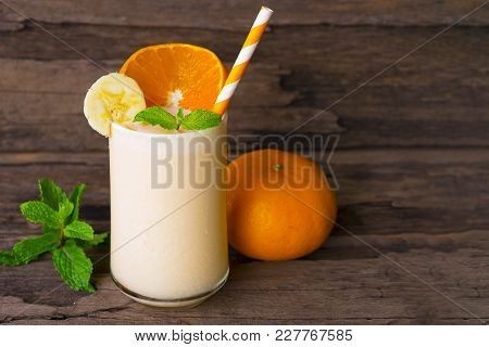 Banana and orange smoothies on a beautiful old wooden background.