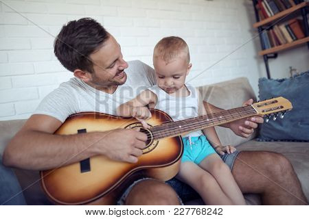 Father Playing  Guitar For His Son.