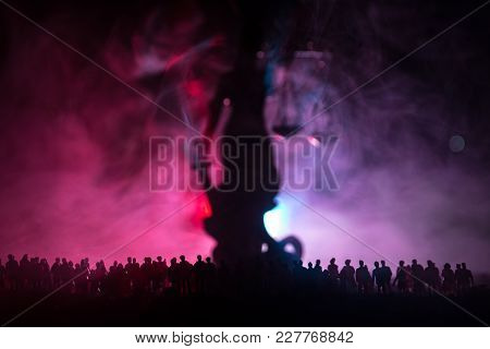 Silhouette Of Blurred Giant Lady Justice Statue With Sword And Scale Standing Behind Crowd At Night