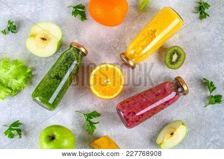 Green, Yellow, Purple Smoothies In Currant Bottles, Parsley, Apple, Kiwi, Orange On A Gray Table. Fl