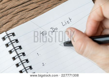Female Hand Holding Black Pen Writing To Do List Prioritized By Number On White Paper Notepad On Woo