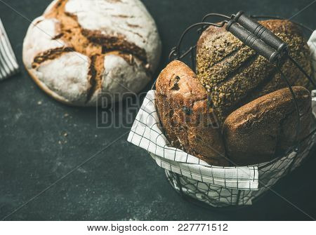 Various Bread Selection. Rye, Wheat And Multigrain Rustic Bread Loaves On Kitchen Towels Over Black