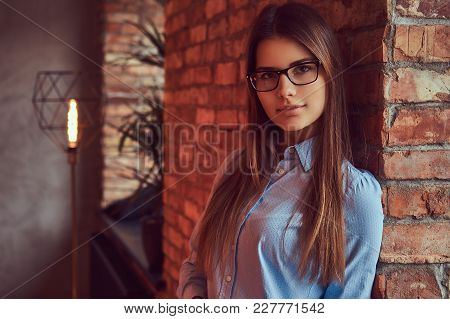 Portrait Of An Attractive Charming Brunette In Glasses And Blue Shirt Leaning Against On A Brick Wal