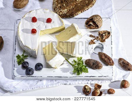Round Camembert Cheese On A White Wooden Board, Next To Sausage And Nuts, White Wooden Table, Top Vi