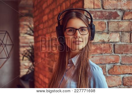 Portrait Of An Attractive Charming Brunette In Glasses And Blue Shirt Listening To Music On Headphon