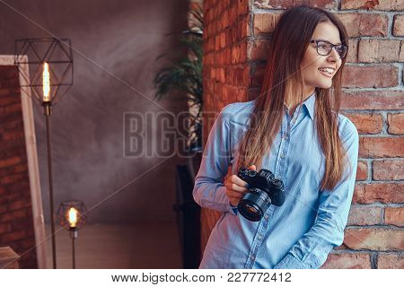 Portrait Of A Young Female Photographer In Glasses And Blue Shirt Smiling Leaning Against On A Brick
