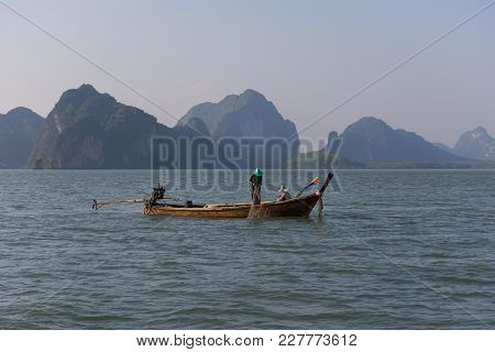 A Fishing Boat And Fishermen Are Working On Catching Fish With Their Fighing Net.