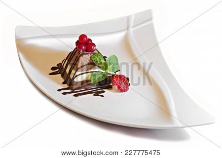 Chocolate Cheesecake With Berries And Syrup On White Background