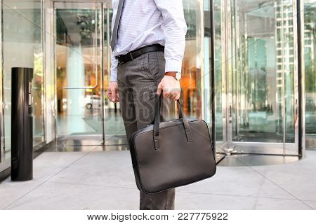 Businessman Standing And Holding A Leather Briefcase In His Hand