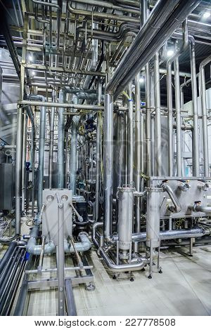 Modern Brewery Interior. System Of Pipelines, Pumps And Vats.