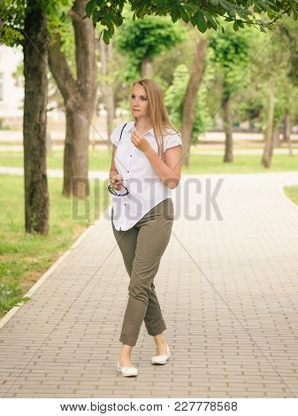 A Beautiful Woman In A White Shirt With A Bag On Her Shoulder Walks In The City Park. Beautiful Woma