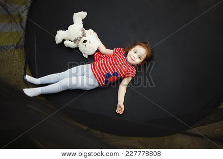 Joyful Child In The Trampoline With Soft Toy. Shot Of Beautiful Girl In Good Mood.
