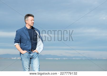 Handsome middle-aged man walking at the beach. Attractive mid adult male model posing at seaside in blue jeans, t-shirt shirt. Outdoor portrait of beautiful macho man.