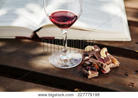 Glass With Red Wine And Pieces Of Chocolate With Nuts And Raisins Stands On Wooden Bar On Background