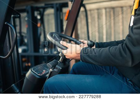 Closeup Man Drives A Reliable Heavy Truck Loader. Heavy Duty Equipment. Tractor Or Roller Paving Veh