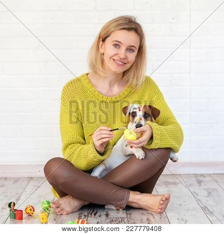 Woman and dog color Easter eggs. Female with pet painting