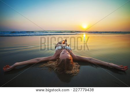 Woman relaxing on the ocean shore. Female lying on the sand on beach. Freedom