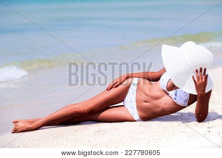 Slim tanned woman on a beach. Summer holidays