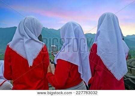JAVA, INDONESIA - DECEMBER 16, 2016: Religious women visiting Prambanan or Candi Rara Jonggrang, a Hindu temple compound in Java, Indonesia