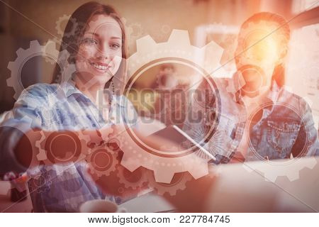 White wheels and cogs on blue against businesswomen shaking hands in creative office